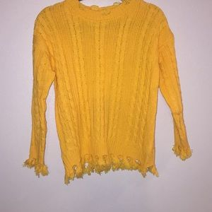 Golden sweater with fringed edges.